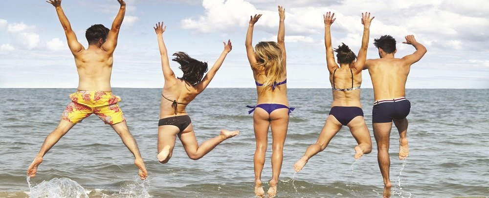 Young people jumping in air at beach